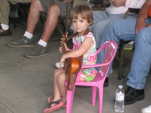 Little girl at the Bluegrass festivals with a guitar